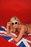 Pretty girl lying on flag Royalty Free Stock Image
