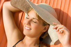 Pretty girl lying in a hammock and tans Royalty Free Stock Photography