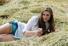 Pretty girl lying on hay one summer day with mobile smart phone Royalty Free Stock Photo