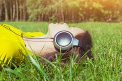 Pretty girl lying with headphones listening to music. Pretty girl lying in summer grass with headphones listening to music and relaxing Stock Photo