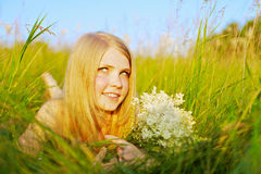 Pretty girl lying in park with flowers Stock Photos