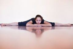 Pretty girl lying and relaxing in the splits. Fitness and yoga coach. Stock Image
