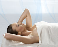 Pretty girl lying on a table with towel and hand o Stock Photography
