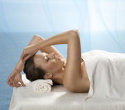 Pretty girl lying on a table with towel and hand o Stock Images