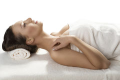Pretty girl lying on a table with towel in profile Royalty Free Stock Images