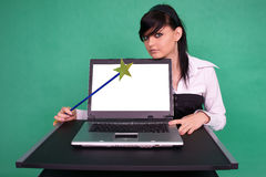 Pretty girl with magic wand and laptop. Royalty Free Stock Photography