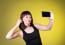Pretty girl make a duck face, and take a self portrait with her smart phone. Sexy brunette Royalty Free Stock Image