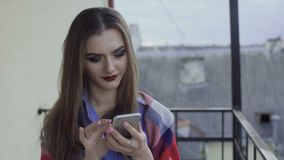 Pretty girl with make-up using smartphone on a balcony 4K.  stock video footage