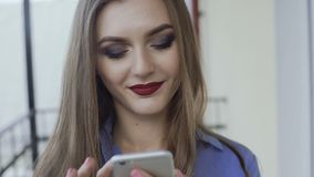Pretty girl with make-up using smartphone on a balcony 4K stock video