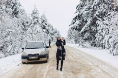 A pretty girl makes photographs on the phone in the middle of a. Snowy forest road near the car stock photography