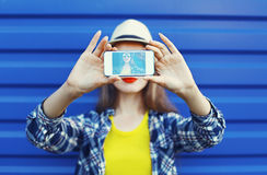 Pretty girl makes self-portrait on the smartphone in the city. Over blue, screen view royalty free stock photos