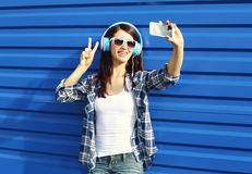 Pretty girl makes self-portrait on smartphone and listens to music in headphones Stock Images