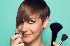 Pretty girl with makeup and makeup accessories. Lipstick, makeup applicator. Pretty girl with makeup accessories and makeup. Girl with short hair. Lipstick Stock Image