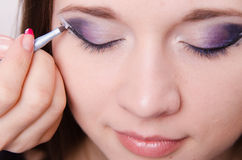 Pretty girl makeup artist draws arrows on eyes Stock Image