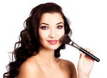 Pretty girl with a makeup brush Stock Image