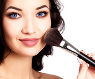 Pretty girl with a makeup brush Royalty Free Stock Photo