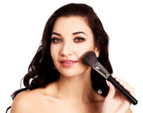 Pretty girl with a makeup brush Royalty Free Stock Image