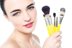 Pretty girl with makeup brushes near her face Royalty Free Stock Photos