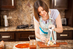 Pretty girl making pizza at home Stock Images