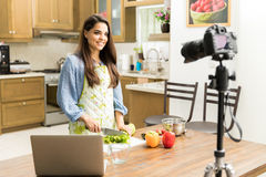 Pretty girl making video for a food blog. Gorgeous young Hispanic woman recording a video for her food blog in a kitchen stock photography
