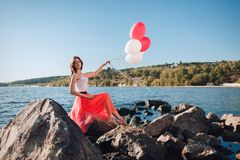 Pretty girl with many colored balloons in hand royalty free stock images