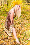 Pretty girl in maple garland. Young woman in autumn park Stock Photography