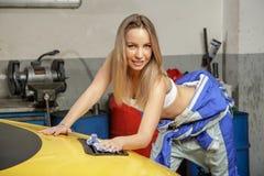 Pretty girl mechanic polishes the car hood Stock Photo