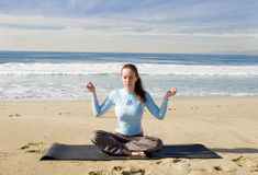 Pretty Girl Meditating at Beach Stock Photos