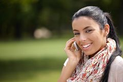 Pretty girl on mobile in park smiling Stock Image