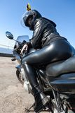 Pretty girl motorcyclist in black leather outfit and helmet sitting on bike, rear view with booty and long legs. Pretty girl motorcyclist in black leather outfit stock images