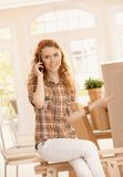 Pretty girl moved to new home smiling using mobile Royalty Free Stock Photo