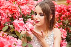 Pretty girl near bush of pink roses Royalty Free Stock Photography