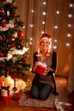 Pretty girl near Christmas tree holding gift Royalty Free Stock Images