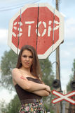 Pretty girl near railroad's traffic sign Royalty Free Stock Images