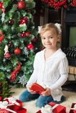 Happy girl in white jacket with gift near christmas tree Stock Photography