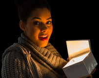 Pretty girl opening a glowing gift Royalty Free Stock Photo