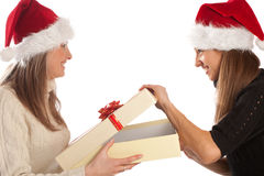 Pretty girl opening Xmas present from her friend Royalty Free Stock Images