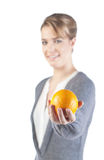 Pretty girl with an orange. Pretty girl holds an orange in her hand; isolated on white background; only orange and hand is in focus Royalty Free Stock Photography