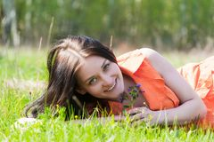 Pretty girl in orange dress laying on grass Royalty Free Stock Images