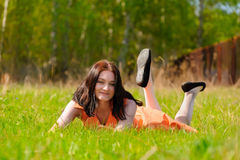 Pretty girl in orange dress laying on grass Stock Photos