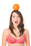 Pretty girl with orange on head fright open mouth Stock Image