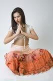 Pretty girl in orange skirt posing in studio. Attractive girl with necklace isolated in studio stock photo