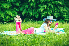 Pretty girl outdoor lying on the grass in the park. Pretty girl lying on the grass outdoor in the park Royalty Free Stock Images