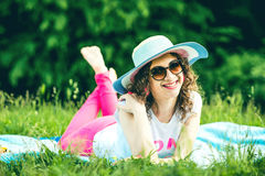 Pretty girl outdoor lying on the grass in the park Stock Images