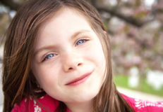 Pretty girl outdoor portrait with cherry blossoms in the backgro Royalty Free Stock Photos