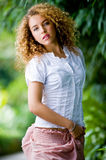 Pretty Girl Outside. A pretty young woman with curly hair outside in park Royalty Free Stock Image