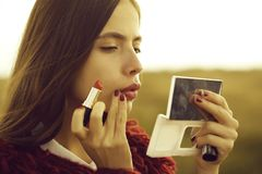Pretty girl paints lips stock photography