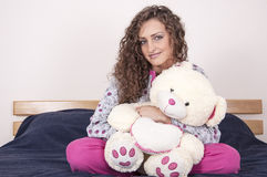 Pretty girl in pajams holding a bear Royalty Free Stock Images
