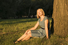 Pretty girl in the Park. Sitting on the grass and basking in the sunlight royalty free stock photography