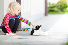 Pretty girl patting a cat outside. Little pretty blond girl patting a cat outside on a garden patio. Summer or spring. Caring. Child connecting with a pet cat Royalty Free Stock Photography